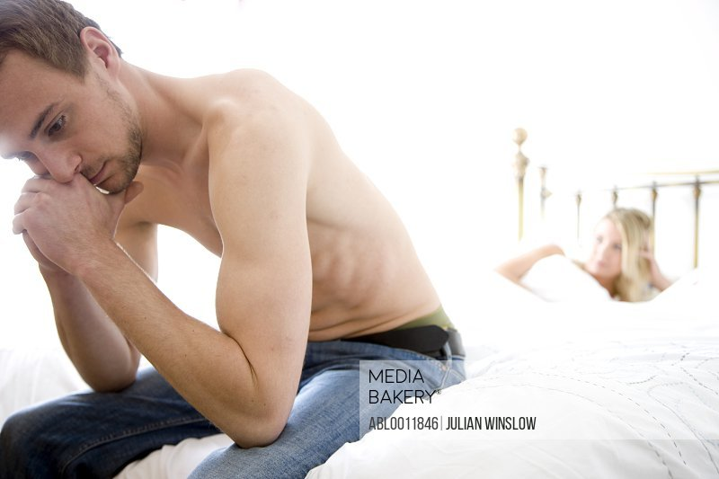 Man sitting at the end of bed with woman lying in bed