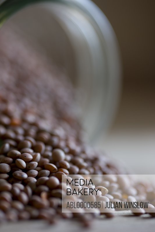 Close up of lentils pouring out of glass jar