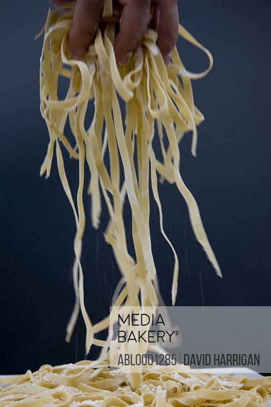 Close up of a hand lifting up some freshly made tagliatelle pasta