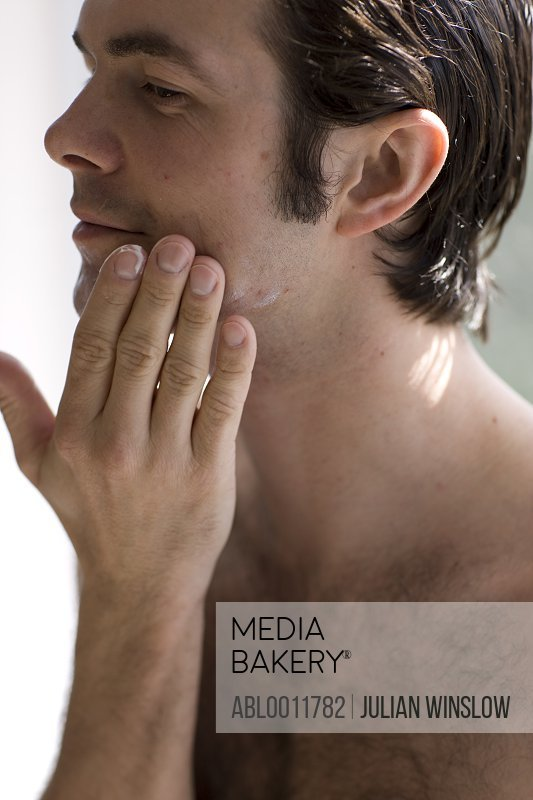 Close up of young man applying moisturizer