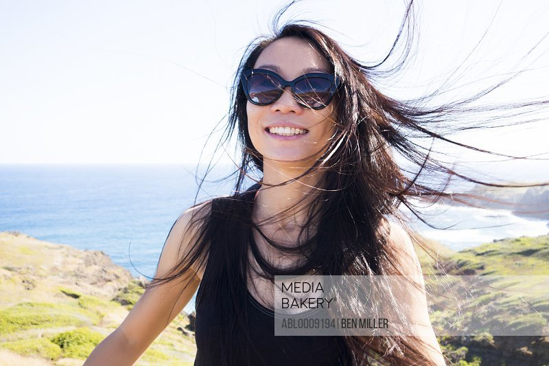 Smiling Woman on Hilltop with Windswept Hair