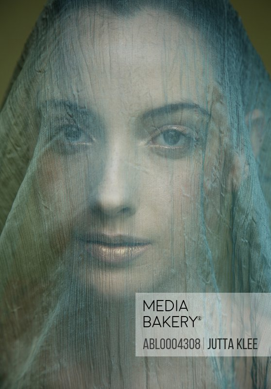 Portrait of young beautiful woman with light green veil