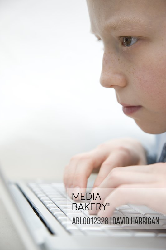 Extreme close up of a boy typing on laptop computer keyboard
