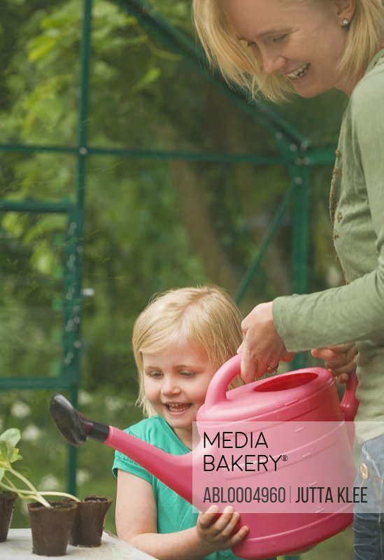 Girl helping woman watering seedling pots in the greenhouse with pink watering can