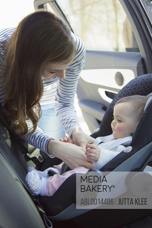 Woman Fastening Baby Girl Safety Seat in Car