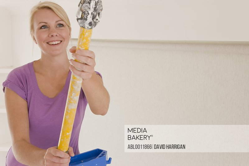Close up of smiling woman holding an extending paint roller