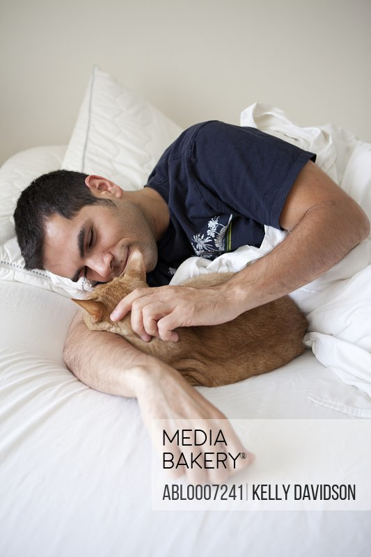 Man Stroking Ginger Cat on Bed