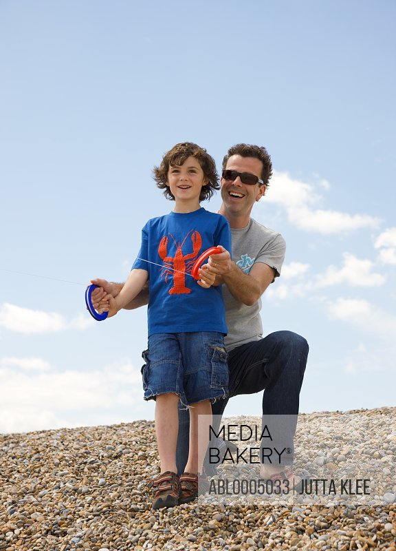 Father and son on a beach holding kite handles