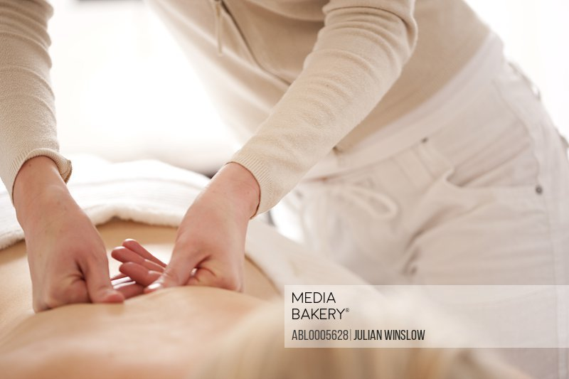 Close up of a masseuse hands giving a woman a back massage