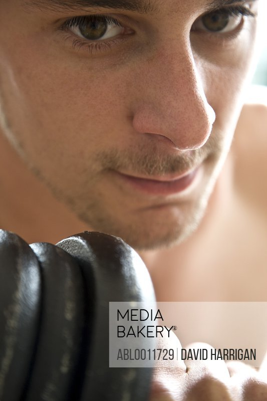 Close up of young man face lifting dumbbell