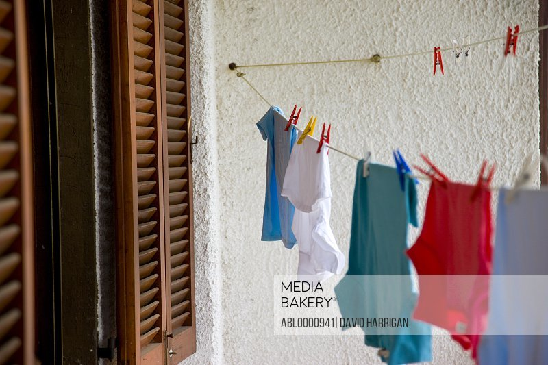 Clothes line with clothes and pegs next to a window with shutters