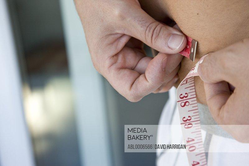 Man Measuring Waist - Close-up view