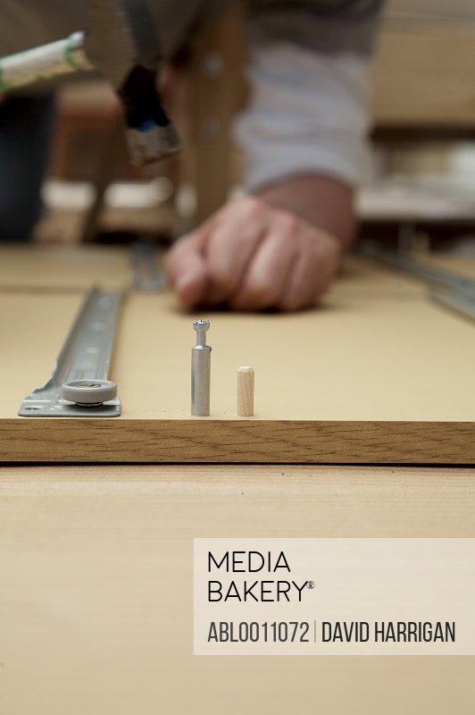 Close up of man's hands building flat pack with hammer