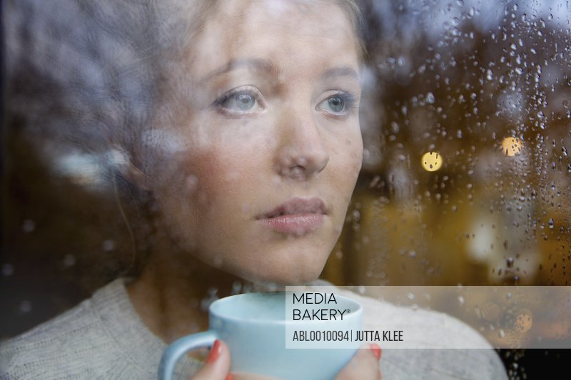 Woman Holding Drinking Cup behind Rainy Window