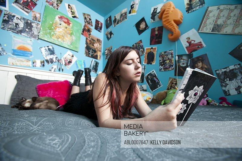 Teenage Girl Lying in Bed Reading