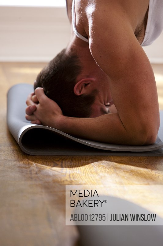 Man practicing yoga in the head-stand position