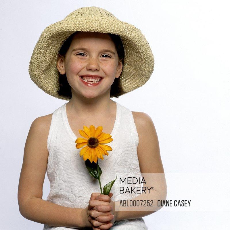 Smiling Girl Wearing Straw Hat Holding Flower