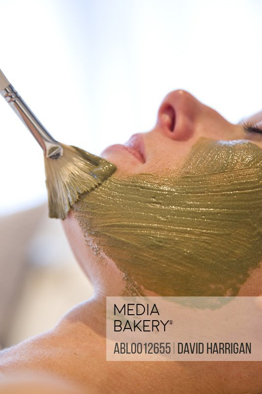 Close up of a brush on a woman face with green beauty mask
