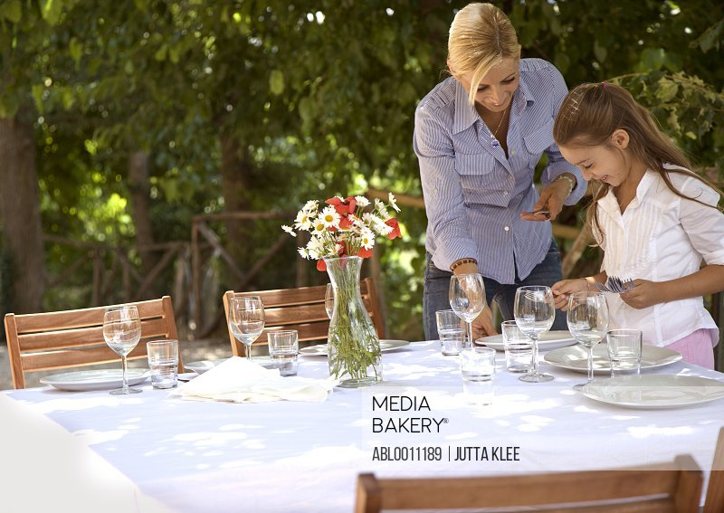 Mother and daughter setting table