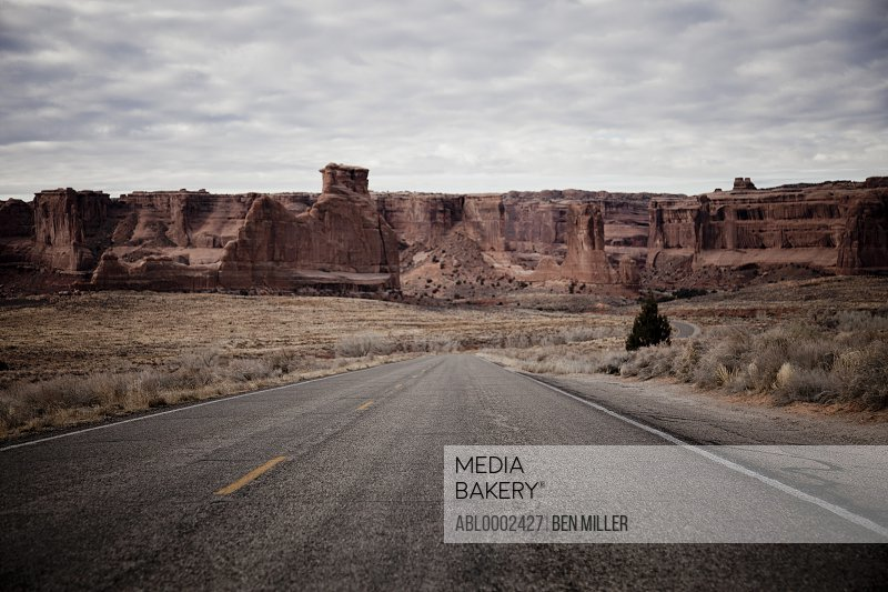 Deserted Road and Sandstone Formations