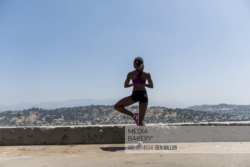 Woman Standing on one leg Looking at View