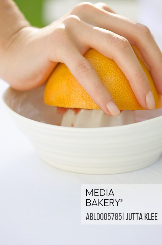 Close up of a woman's hand squeezing an orange on a juicer