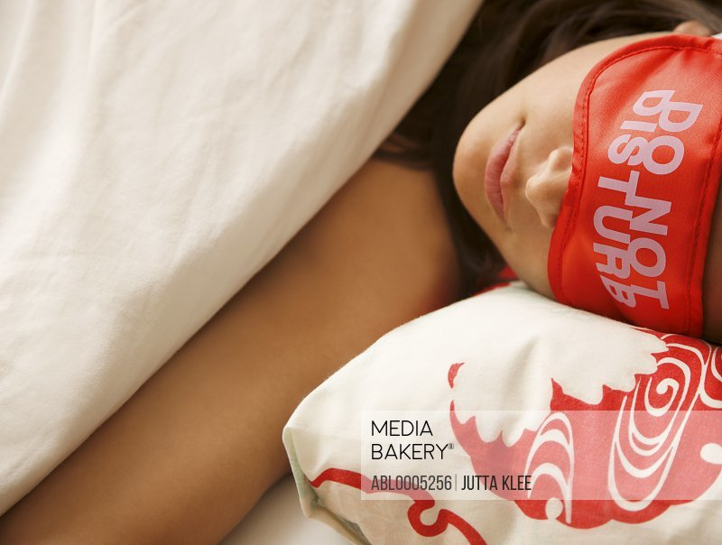 Young woman sleeping and wearing a do not disturb sleep mask