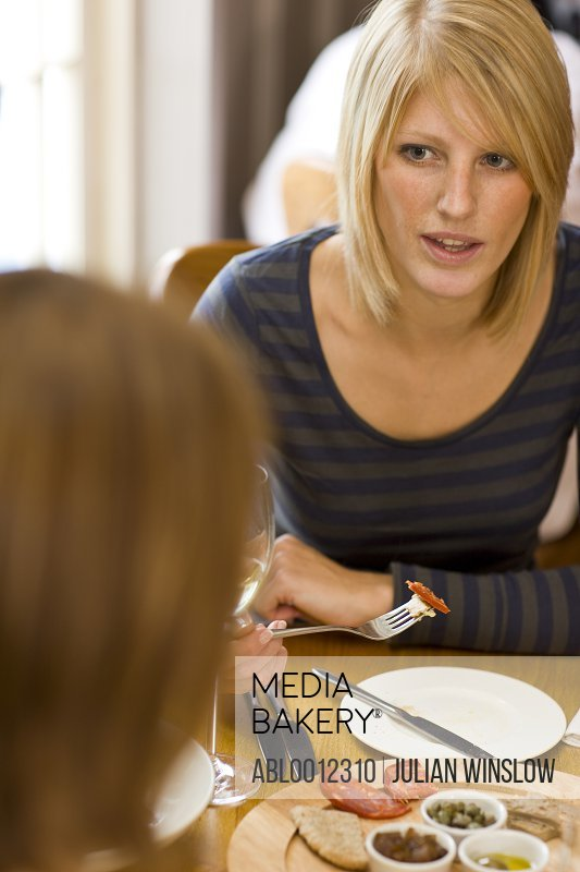 Woman sitting at a dining  table eating
