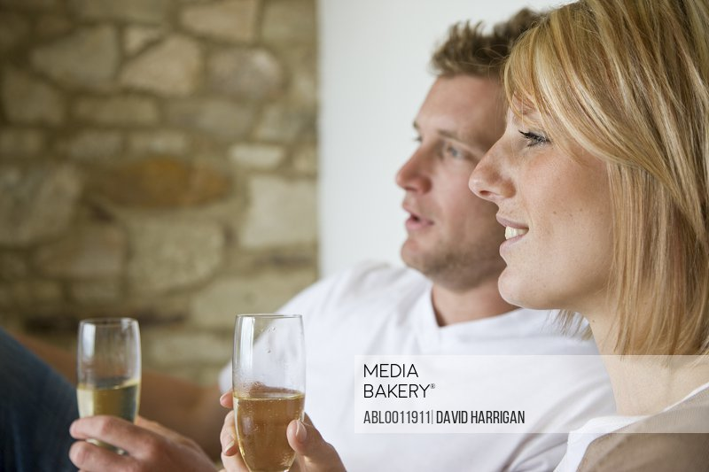 Close up profile of young couple sitting and holding champagne glasses