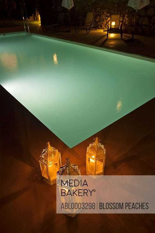 Candles Burning in Lanterns by Illuminated Swimming Pool