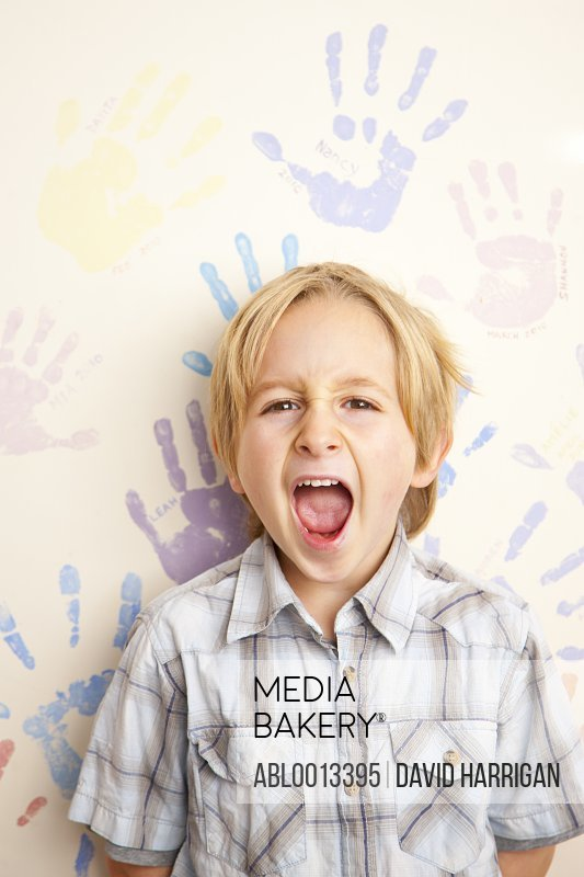 Screaming Boy Standing in front of Wall Covered in Handprints