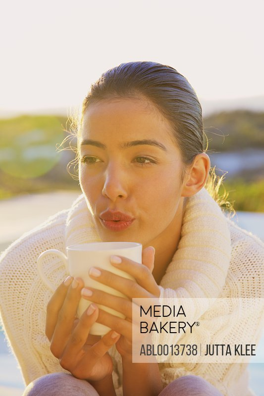 Young Woman Blowing on Hot Drink