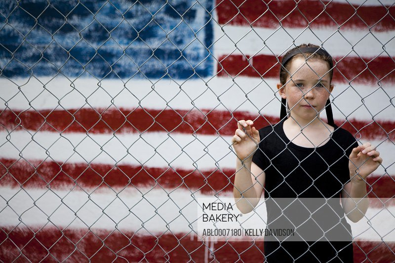 Girl Standing Behind Chain Link Fence with Mural of American Flag in Background