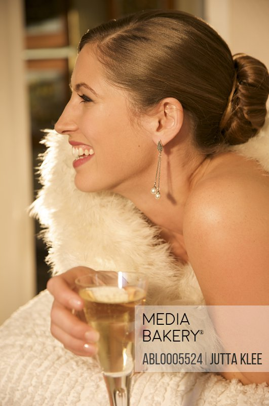 Profile of a woman wrapped in a swan feather stole holding a glass of champagne
