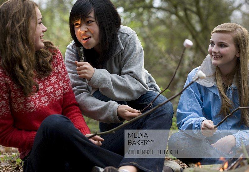 Teenage girls roasting marshmallow over campfire