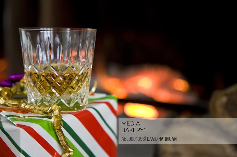 Close up of a glass of whiskey on a gift box  in front of a log fire