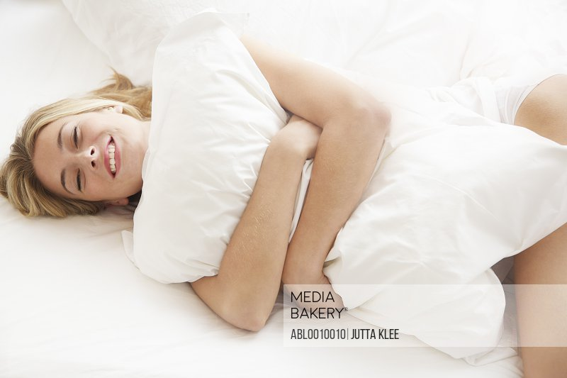 Woman Lying on Bed Hugging Pillow