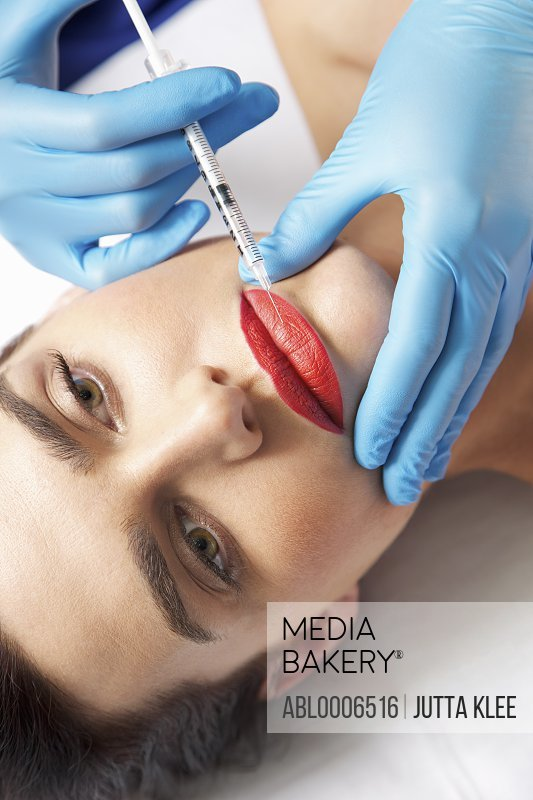 Woman Receiving Botox Injection on Lips - Close-up view