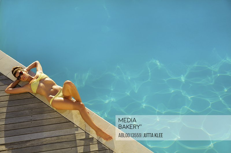 Woman Sunbathing by Swimming Pool, High Angle View