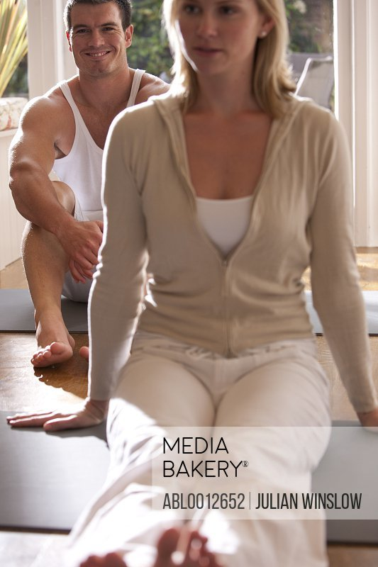 Smiling man and woman sitting on yoga mats