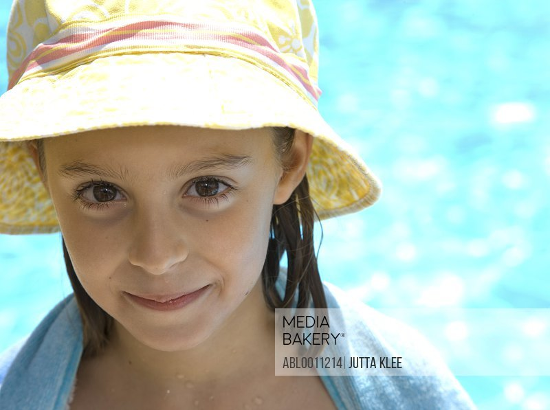 Young girl with hat and towel around shoulders