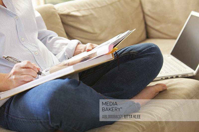 Woman Sitting Cross Legged Writing on Note Pad, Close-up view