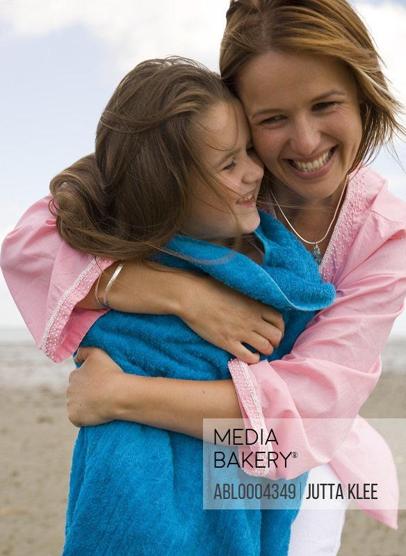 Mother drying and embracing daughter with blue towel