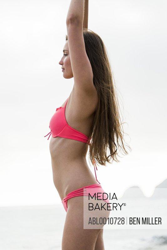 Side View of Young Woman on Beach Wearing Bikini