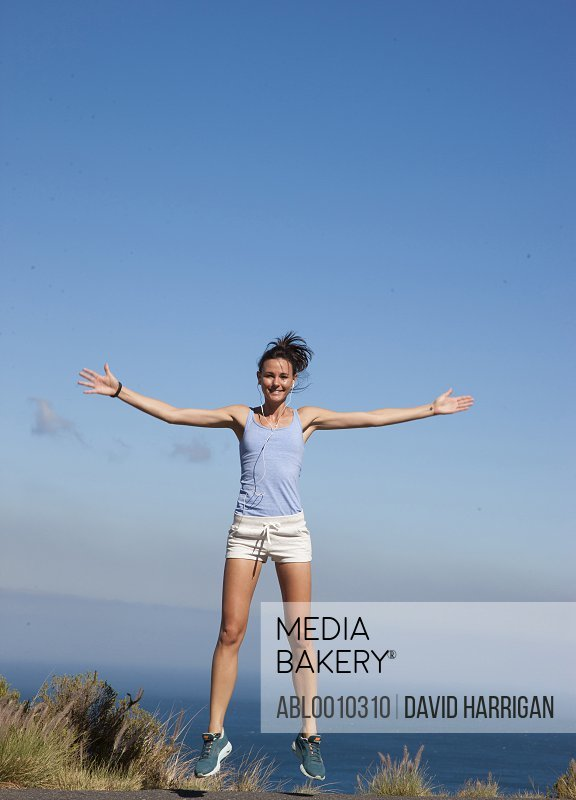 Sport Woman Jumping Mid-air against Ocean and Blue Sky