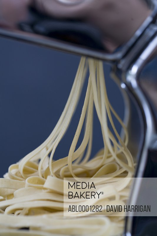 Heap of fresh tagliatelle coming out of a pasta maker