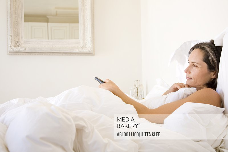 Woman lying in bed changing channel with remote control