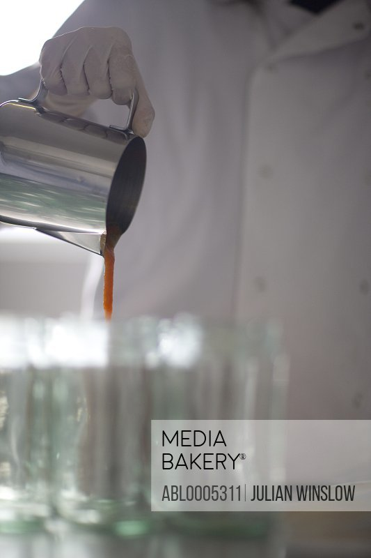 Close up of a factory worker pouring tomato sauce into glass jars