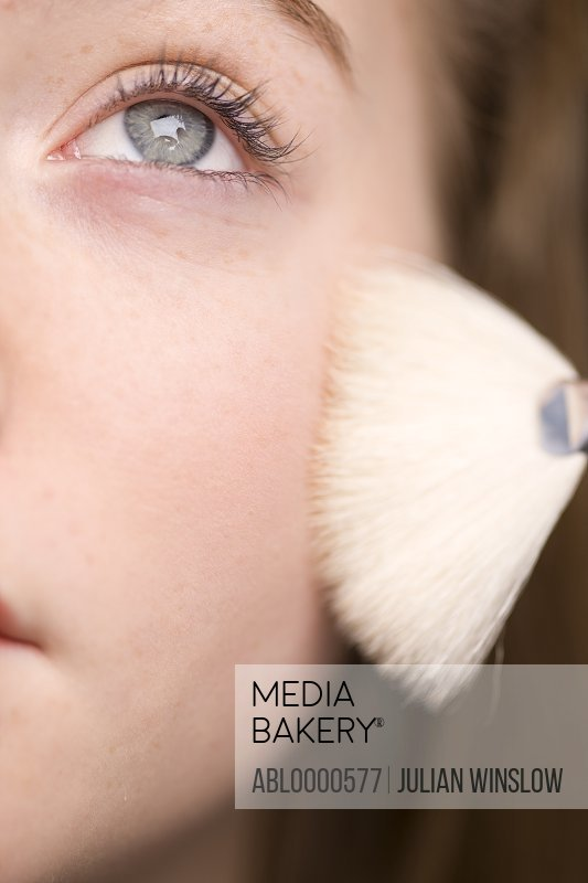Close up of young woman applying powder blush with white make-up brush