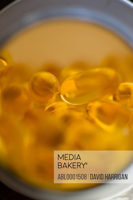 Extreme close up of an open pill bottle full of cod liver oil capsules